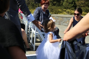 The darling flower girl walking down the aisle to her mom and grandma.